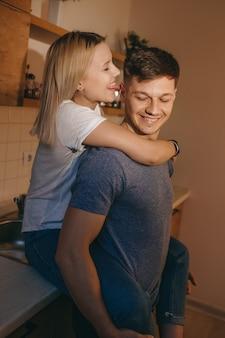 キッチンに座って一緒に遊んでいる恋人を抱きしめる元気な女の子