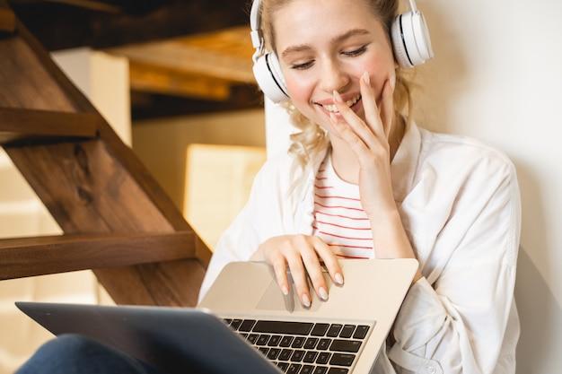 Веселая девушка выражает позитив, глядя на экран своего ноутбука