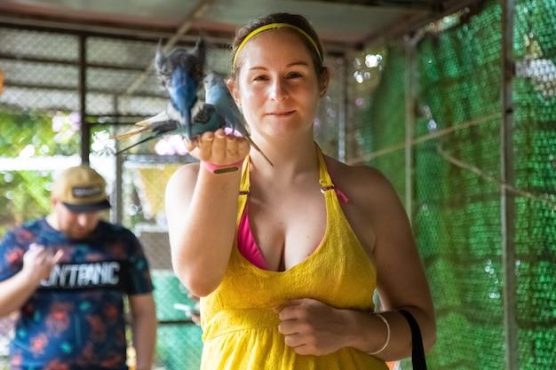 陽気な女の子は彼女の手からオウムを養い、笑います。動物園にお問い合わせください。