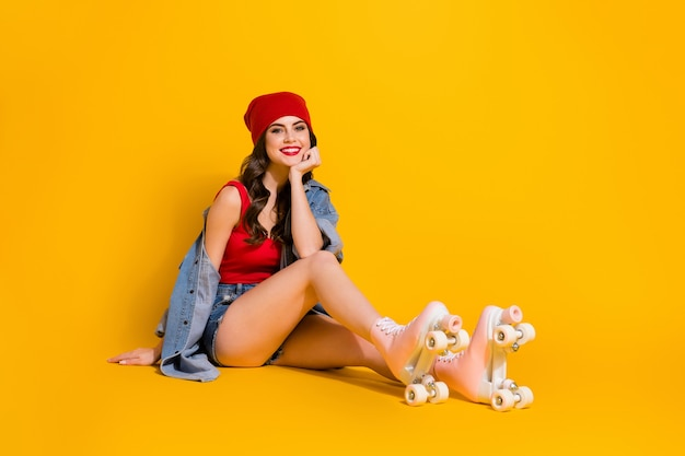 Cheerful girl fit roller skater sit floor free time