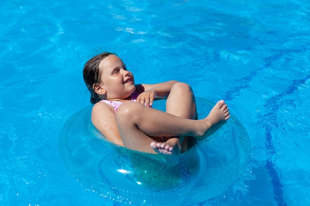 Cheerful girl floating crosslegged and eyes closed on a blue inflatable circle in the hotel pool on ...