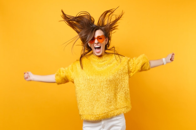Cheerful girl in fur sweater and heart orange glasses screaming fooling around in studio jumping with flowing hair isolated on yellow background. people sincere emotions, lifestyle. advertising area.
