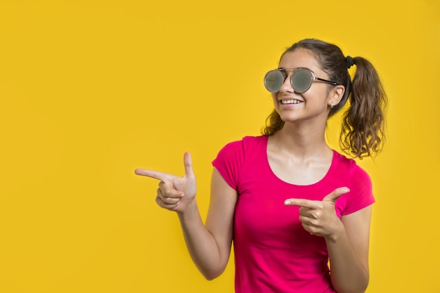 A cheerful girl in glasses points her fingers at copy space.