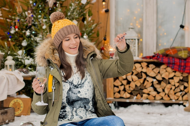 Cheerful girl  hat down jacket with sparklers with glass champagne her hand celebrates chr