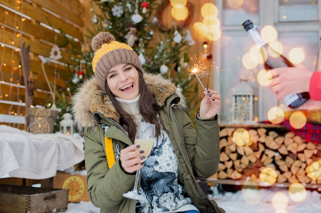 Cheerful girl hat  down jacket with sparklers with glass champagne in her hand celebrates