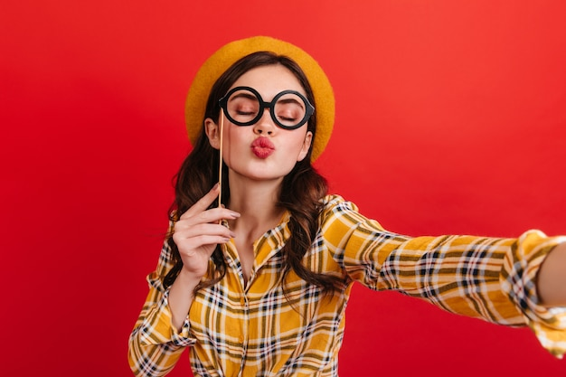 Cheerful girl in hat holds glasses on stick and sends kiss. teen in yellow shirt takes selfie on red wall.