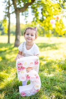 Веселая девушка веселится на детский день рождения на одеяле с бумажными украшениями в парке