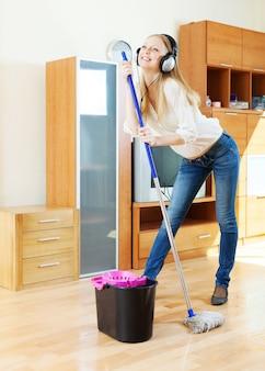 Cheerful girl in headphones washing floor