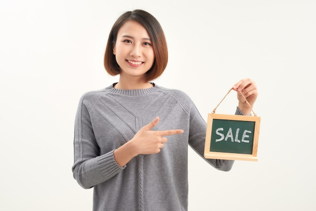 Cheerful girl holding  advertising board with sale word and pointing on it, white studio background
