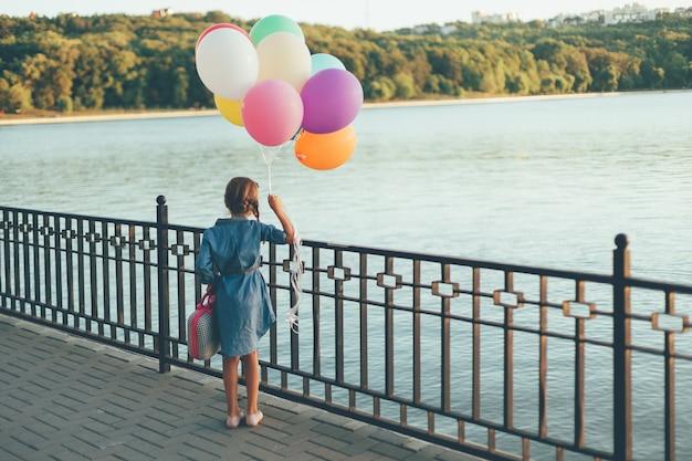 다채로운 풍선과 유치 한 가방을 들고 명랑 소녀