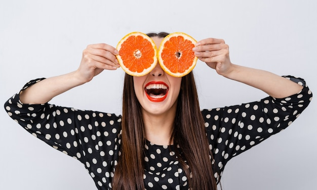 Cheerful girl holding grapefruit halves near eyes. concept of crazy vegan person. facial expressions.