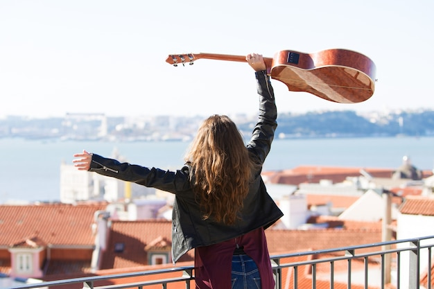 Cheerful girl holding guitar above head on rooftop
