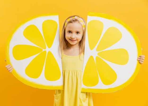 Веселая девушка держит ломтики лимона украшения