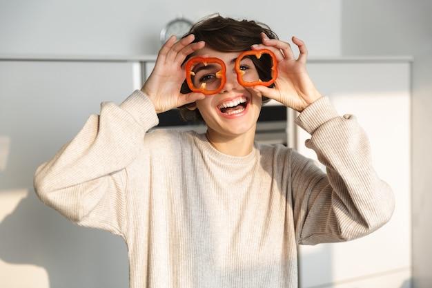 Жизнерадостная девушка держит нарезанный перец у лица, стоя на кухне