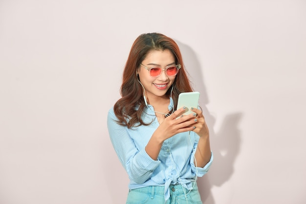 明るい背景でselfieを撮影手にスマートフォンを持っている陽気な女の子