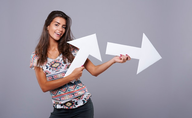 Cheerful girl holding vertical and horizontal arrow signs