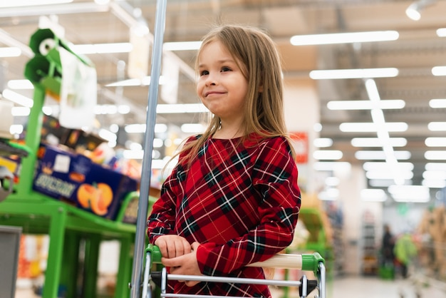 A cheerful girl holds a cart and selects products home. the concept of shopping at the supermarket, selection of products, sales