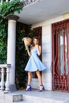 Жизнерадостная девушка в синем платье с красными губами и стильной прической