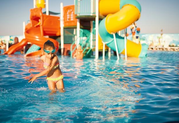 明るい水着と青い水泳用ゴーグルを着た陽気な女の子が、水に手を入れて澄んだ水でプールで回転しています