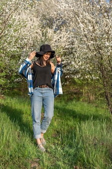 春に咲く木々に囲まれた帽子をかぶった陽気な女の子、カジュアルなスタイル。