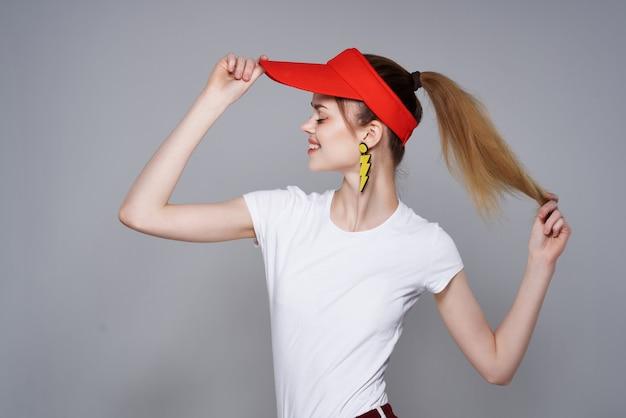 夏のスタイルのポーズをとって髪を保持している赤い帽子の陽気な女の子