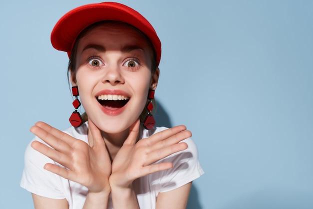 赤い帽子のメイクアップファッショングラマーブルーの背景で陽気な女の子