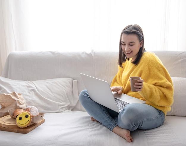 黄色いセーターを着た陽気な女の子は、自宅のソファで離れた場所で働いています。仕事中にコーヒーを飲みます。