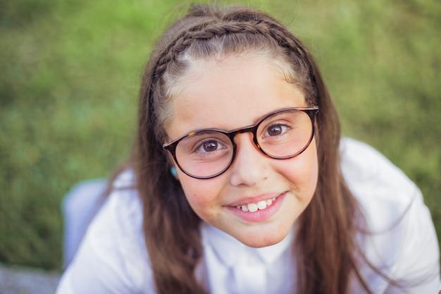 見て、笑っている茶色の目を持つ眼鏡の陽気な女の子