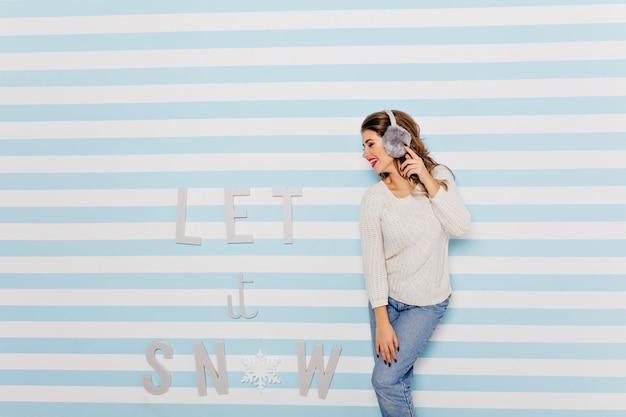 ふわふわの灰色のヘッドフォンで陽気な女の子は、肖像画のプロファイルでポーズします。白いセーターのかわいいモデルが笑う