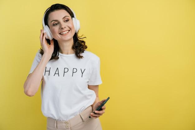 ヘッドフォンで陽気な女の子が携帯電話を持って目をそらします。