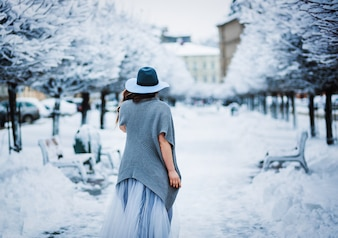 Cheerful girl in light summer dress, sweater and hat walks along the park alley