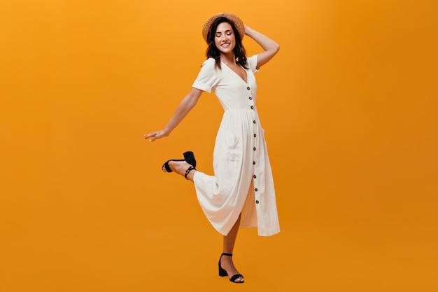 Жизнерадостная девушка в мини-платье и шляпе кокетливо поднимает ногу на оранжевом фоне