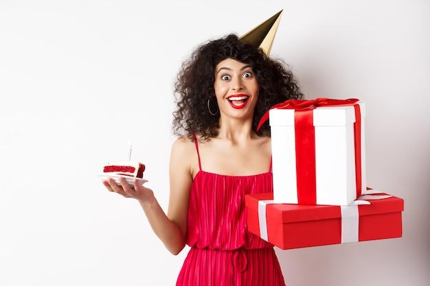 パーティーハットと赤いドレスを着た陽気な女の子、誕生日を祝う、サプライズギフトとb-dayケーキを保持し、休日を楽しんで、白い背景の上に立っています。