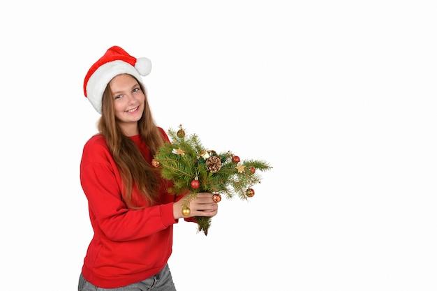 Веселая девушка в новогодней шапке в красном пуловере с ветками елки