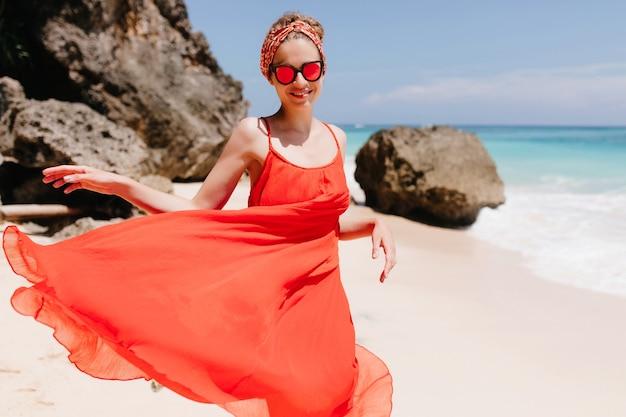 海の岩の近くで誠実な笑顔でポーズをとるスパークルサングラスの陽気な女の子。オーシャンビーチで晴れた日に幸せを表現する楽しい若い女性の写真。