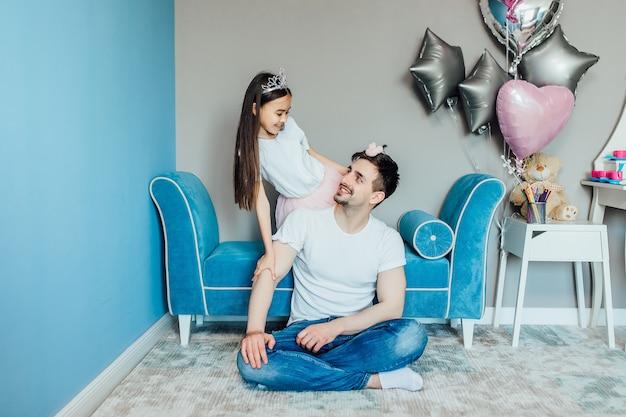 La ragazza allegra sta mostrando a suo padre la sua acconciatura