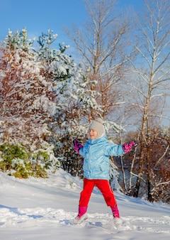 晴れた冬の日に雪の中でジャンプする陽気な少女。雪のあるアクティブなゲーム。冬休み。
