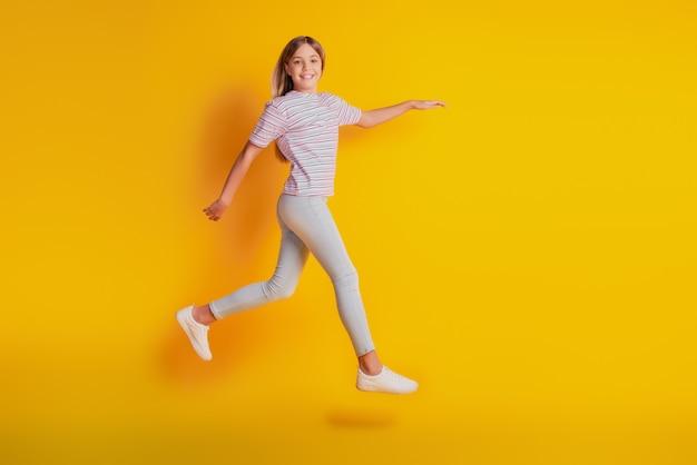 Веселая девушка прыгает, работает, изолированные на желтом фоне