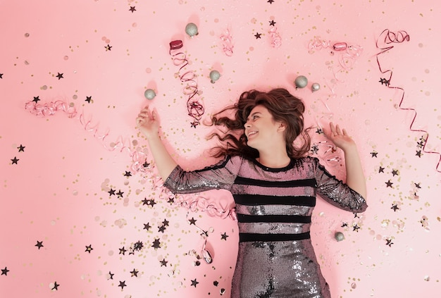 Веселая девушка лежит на розовом фоне среди конфетти и серпантина, вид сверху