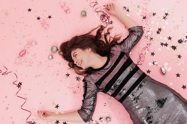 La ragazza allegra giace su uno sfondo rosa tra i coriandoli e la vista dall'alto a serpentina