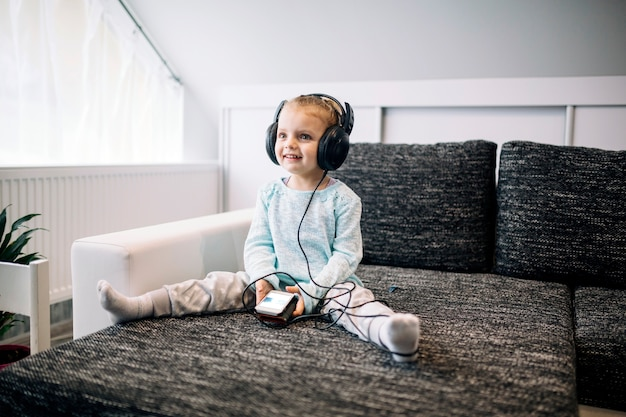 Cheerful girl listening to music on couch