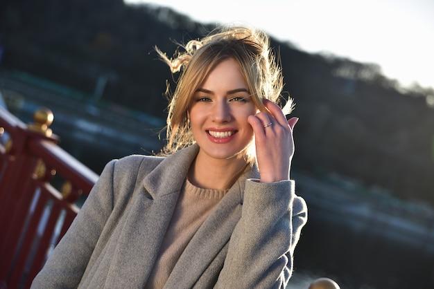 陽気な女の子は美しい晴れた日にカメラを見てください。日当たりの良いムードを楽しむ