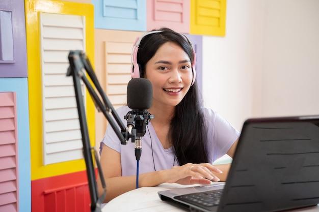ノートパソコンを使用しながらカメラを見て、マイクロフに話している間ヘッドフォンを着用している陽気な女の子...