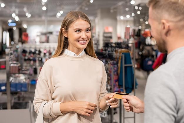 陽気な女の子が彼氏を笑顔で見ながら、ショッピングモールで販売されているものを購入するのにクレジットカードを使う