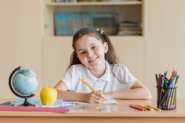 Cheerful girl looking at camera during lesson
