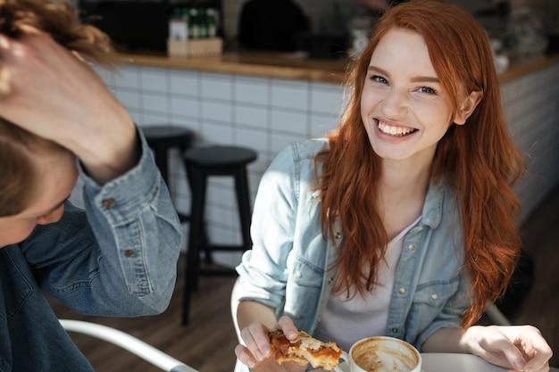 Веселая девушка смотрит камеру в кафе