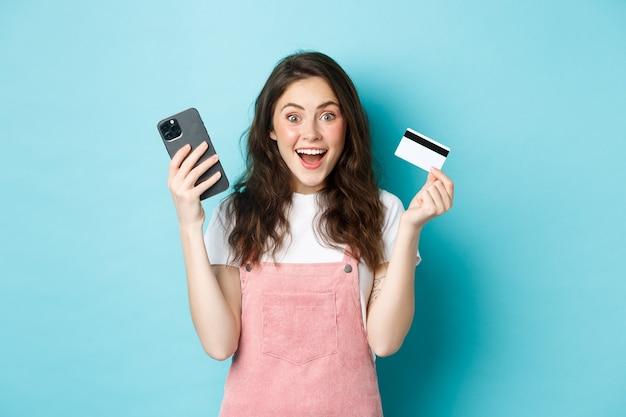 陽気な女の子はカメラに興奮しているように見えます、スマートフォンとプラスチックのクレジットカードを持って、青い背景の上に立っています