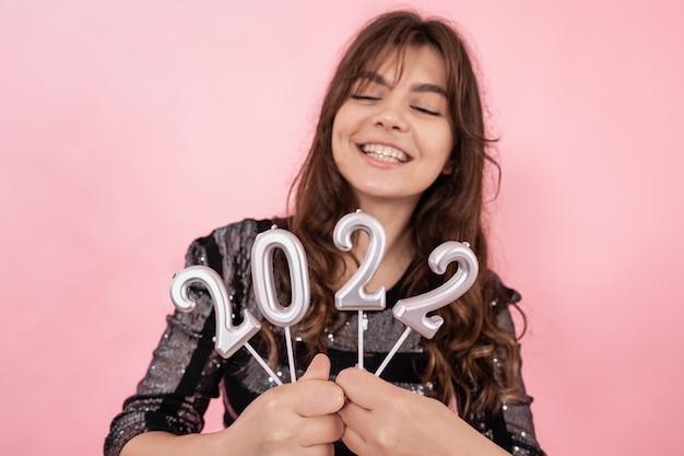 ピンクの背景の陽気な女の子は微笑んで、彼女の手で数字2022を保持し、新年を祝います。