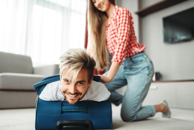 Веселая девушка упаковала мужа в чемодан