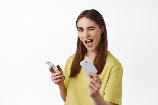 Веселая девушка платит по телефону, делает покупки в интернете со смартфона, показывает кредитную карту и подмигивает, получила кэшбэк за покупку, стоя на белом